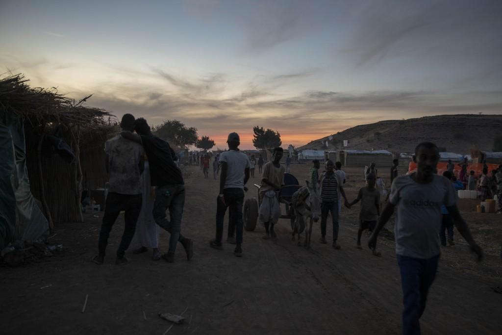 People who fled the conflict in the Tigray region of Ethiopia, walk in Umm Rakouba refugee camp, in Qadarif, eastern Sudan, Monday, Dec. 14, 2020. (AP...