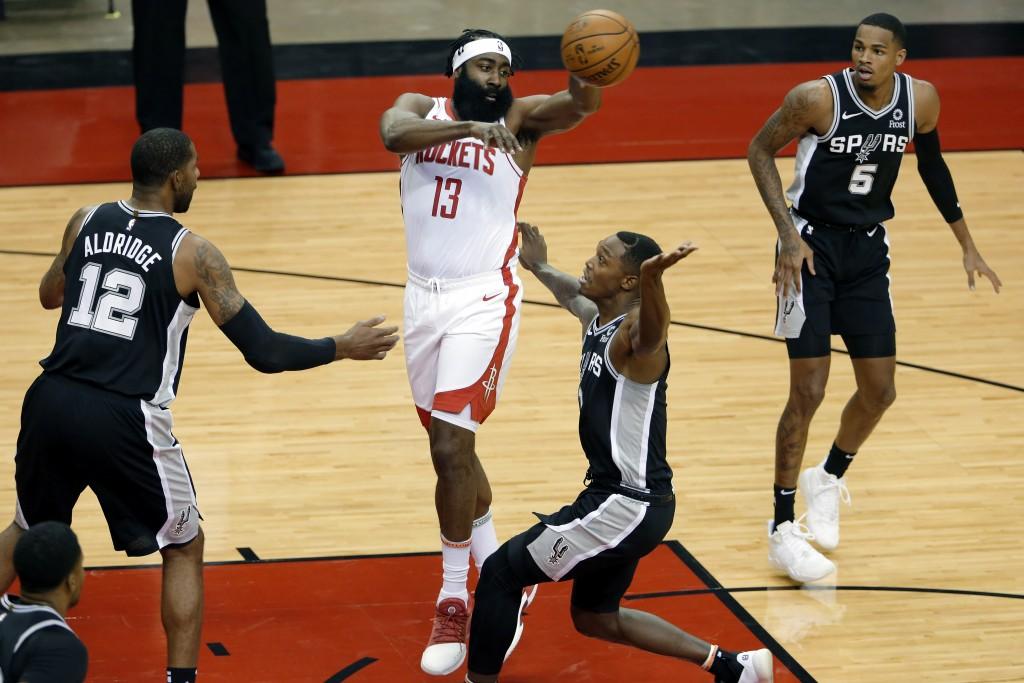 Houston Rockets guard James Harden (13) passes the ball over San Antonio Spurs forward LaMarcus Aldridge (12), guards Lonnie Walker IV, middle right, ...