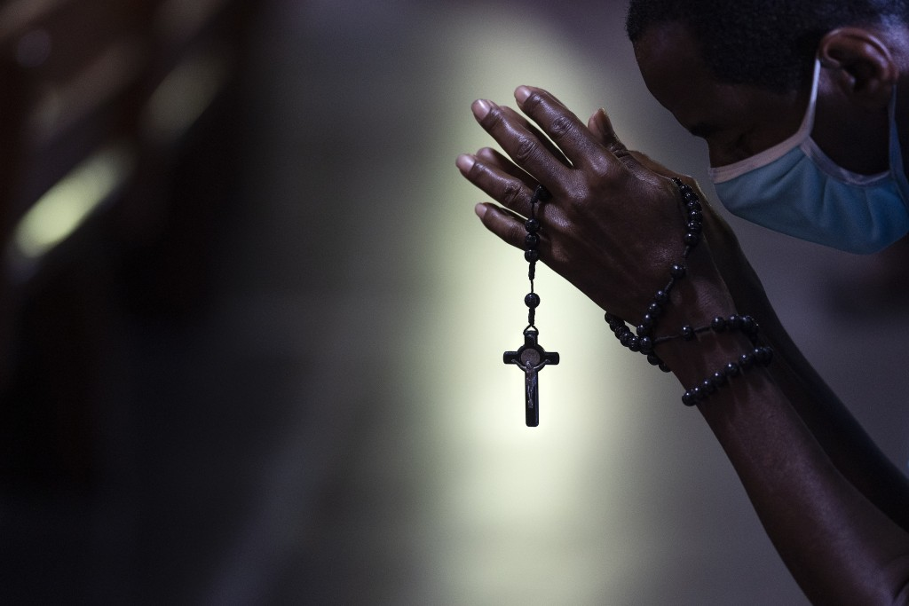 With rosary beads wrapped around clasped hands, a man bows in prayer during a Mass at the Metropolitan Cathedral, in Rio de Janeiro, Brazil, Saturday,...
