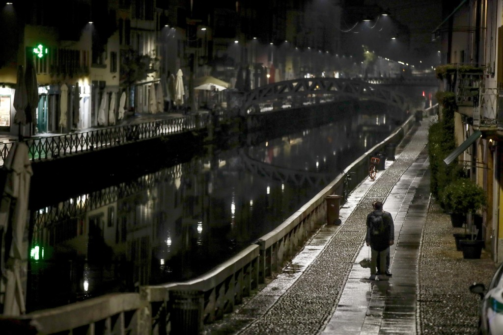 A man stands on the unusually empty Navigli area, a popular evening spot of restaurants and pubs along canals in Milan, Italy, Thursday, Oct. 22, 2020...