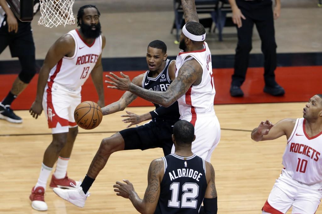 San Antonio Spurs guard Dejounte Murray (5) dishes the ball off to San forward LaMarcus Aldridge (12) around Houston Rockets center DeMarcus Cousins (...
