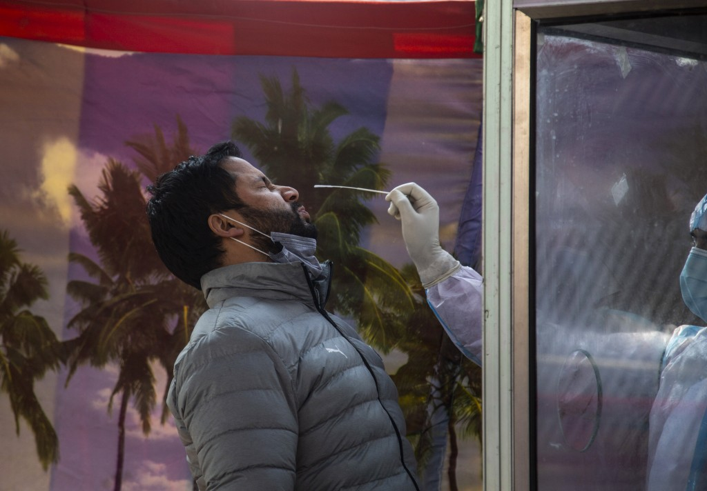 A Kashmiri man reacts as a health worker takes his nasal swab sample to test for COVID-19 in Srinagar, Indian-controlled Kashmir, Wednesday, Dec. 16, ...