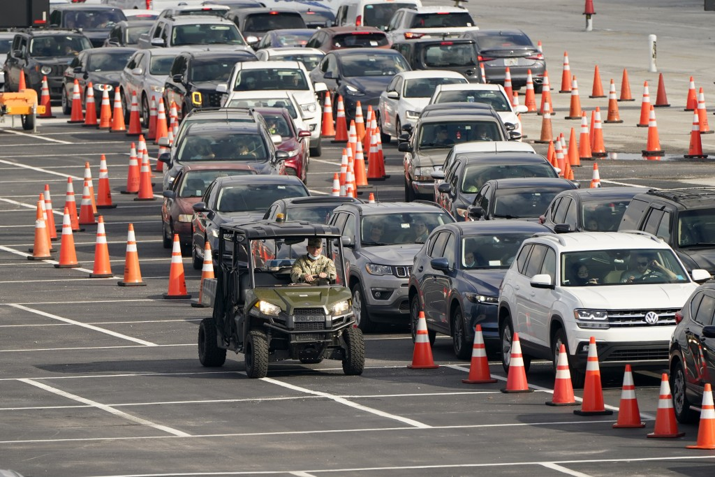 FILE - In this Nov. 23, 2020, file photo, vehicles wait in line at a COVID-19 testing site at Hard Rock Stadium in Miami. After a punishing fall that ...