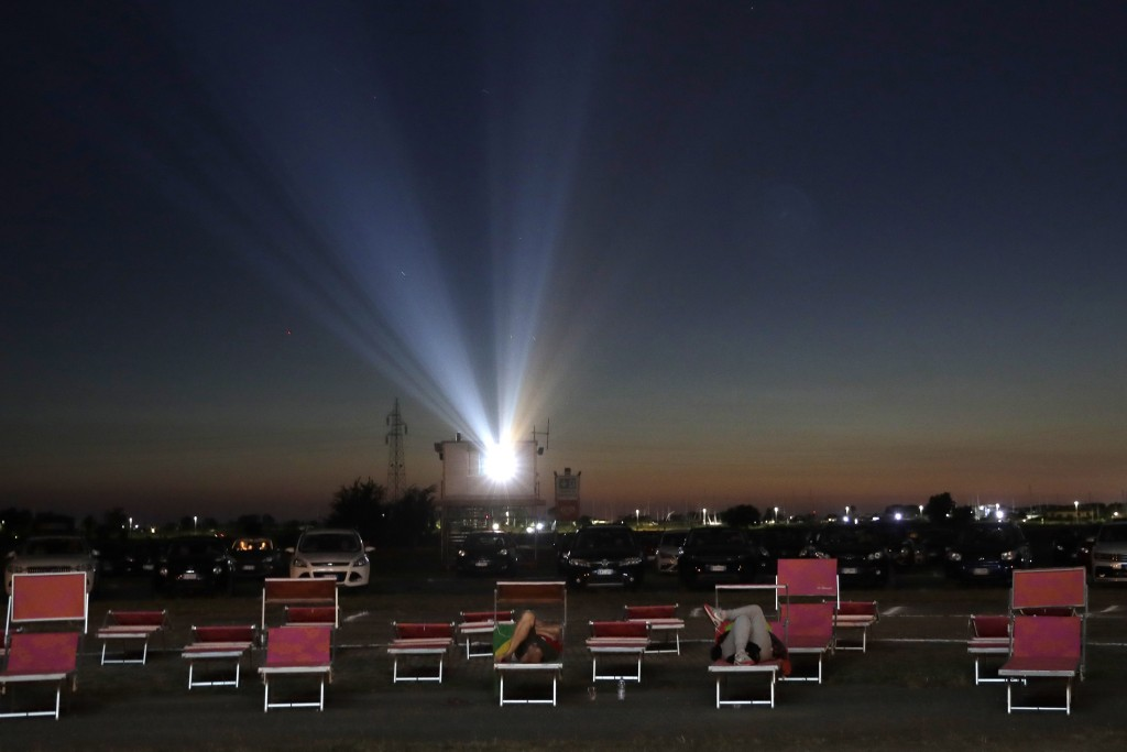 """People in their cars and on lounging chairs watch the movie """"Tolo Tolo"""" at the Paolo Ferrari drive-in cinema in Ostia, on Rome's seaside on Thursday, ..."""