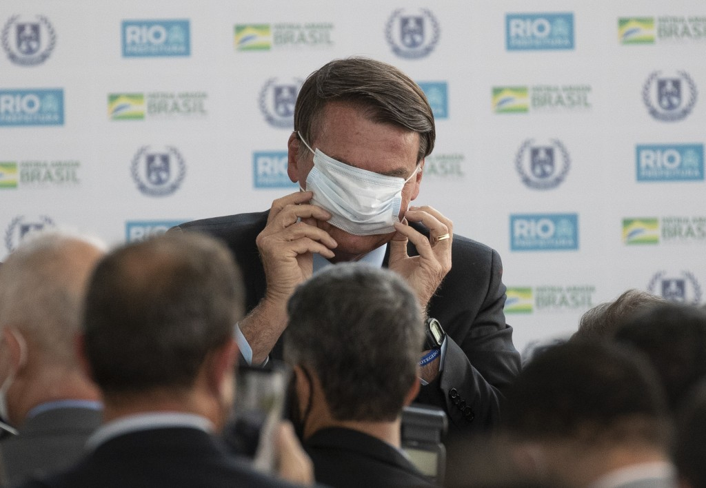 Brazil's President Jair Bolsonaro puts on a mask due to the COVID-19 pandemic during the inauguration of the new General Abreu civic-military school i...