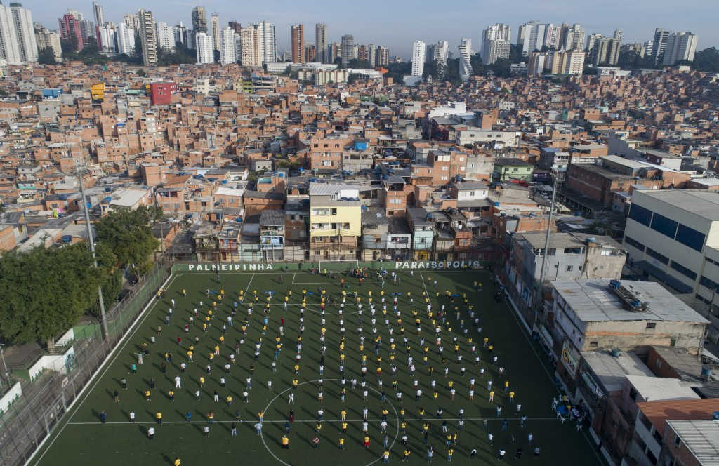 Residents of the Paraisopolis slum attend a ceremony on a soccer field after getting basic training from health workers on how to stay safe in their c...