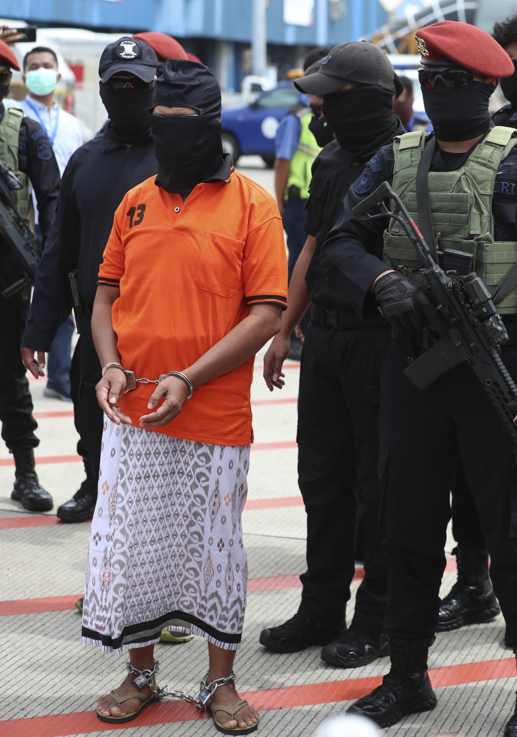 Police officers escort suspected militant Zulkarnaen, center, who is also known as Aris Sumarsono, upon arrival at Soekarno-Hatta International Airpor...