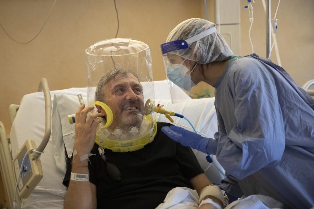 Patient Nazzareno Santilli, 60, under oxygen CPAP (continuous positive air pressure) headgear ventilation, smiles with Dr. Elisabetta Teti in the sub-...