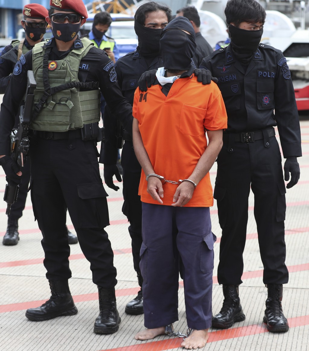 Police officers escort suspected militant Upik Lawanga, center, upon arrival at Soekarno-Hatta International Airport in Tangerang, Indonesia, Wednesda...