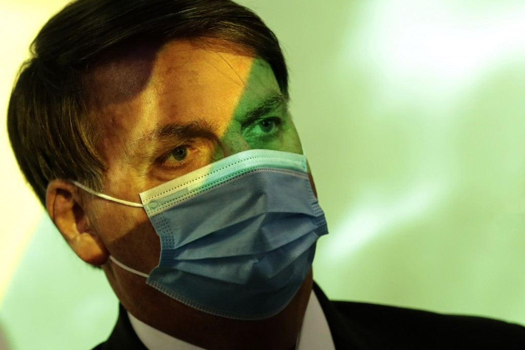 President Jair Bolsonaro wears a mask amid the COVID-19 pandemic at the start of a ceremony where the national flag is projected in Brasilia, Brazil, ...