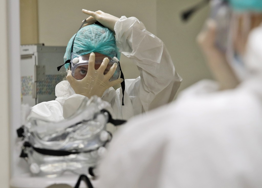 Nurse Ginevra Fattori adjusts her protective equipment before entering the sub-intensive care unit of the San Filippo Neri hospital in Rome, Thursday,...