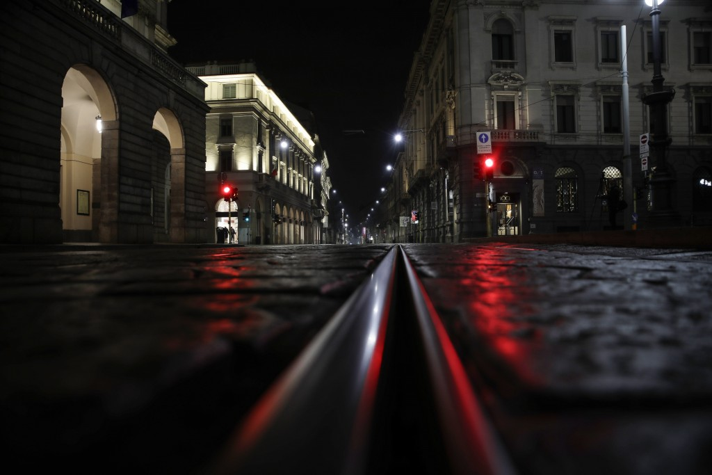 Light reflects off the cobblestones of an empty street next to La Scala theater, left, early Sunday, Oct. 25, 2020. On its second night of curfew, Mil...