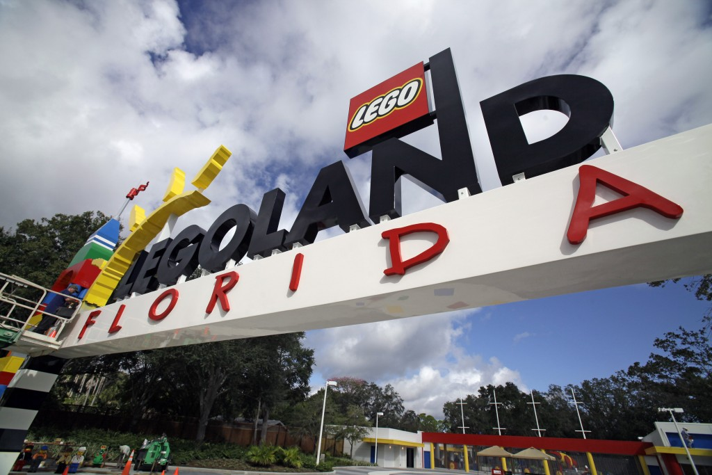 FILE - In this Tuesday, Sept. 27, 2011, file photo, a worker puts finishing touches on the entrance sign at Legoland Florida in Winter Haven, Fla. The...
