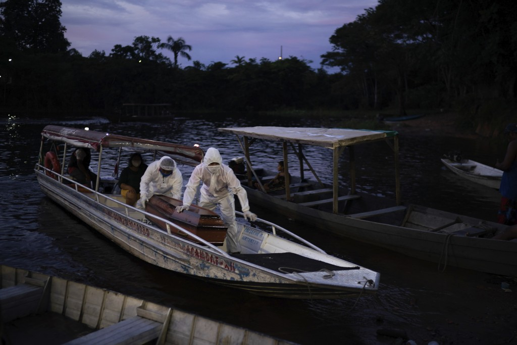SOS Funeral workers use a boat to transport a coffin carrying the body of an 86-year-old woman who lived by the Negro River and is a suspected to have...