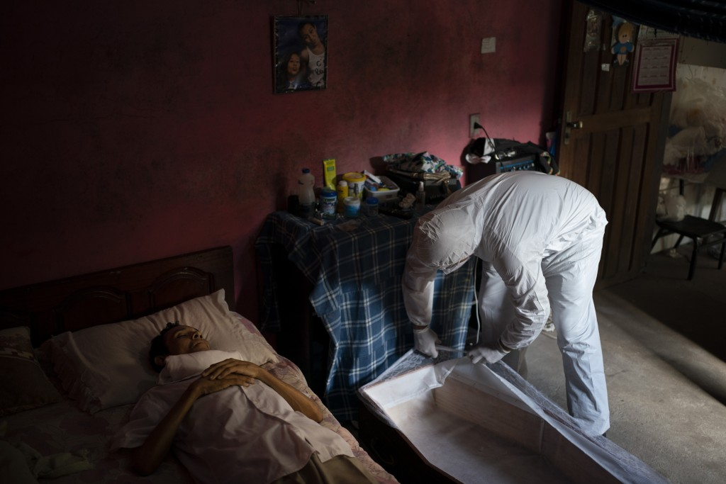 An SOS Funeral worker wearing protective equipment amid the new coronavirus pandemic prepares to remove the body of Eldon Cascais in Manaus, Brazil, S...