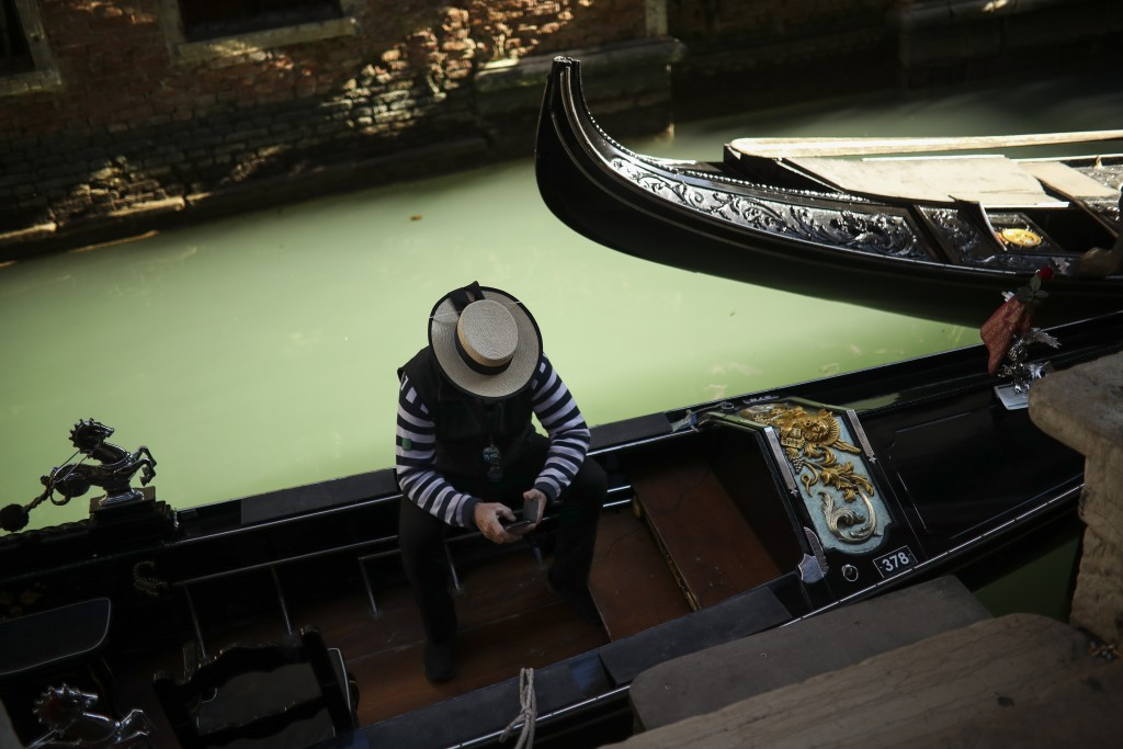 A gondolier looks at his smartphone as he waits for clients in Venice, Italy, Friday, Feb. 28, 2020, during the coronavirus outbreak. (AP Photo/Franci...