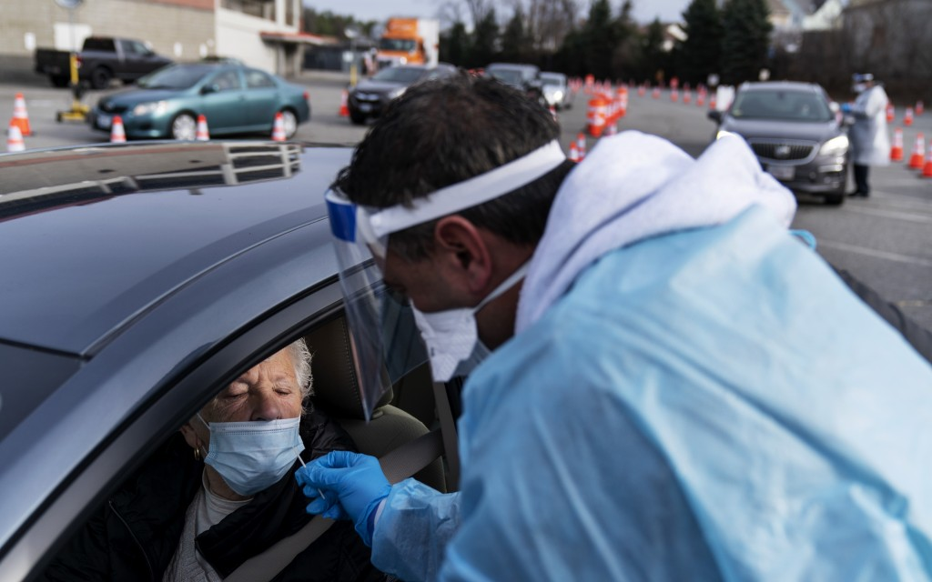 FILE - In this  Dec. 9, 2020, file photo, Beverly Palazzi is swabbed for COVID-19 by Milton Giard at a testing site set up outside McCoy Stadium in Pa...