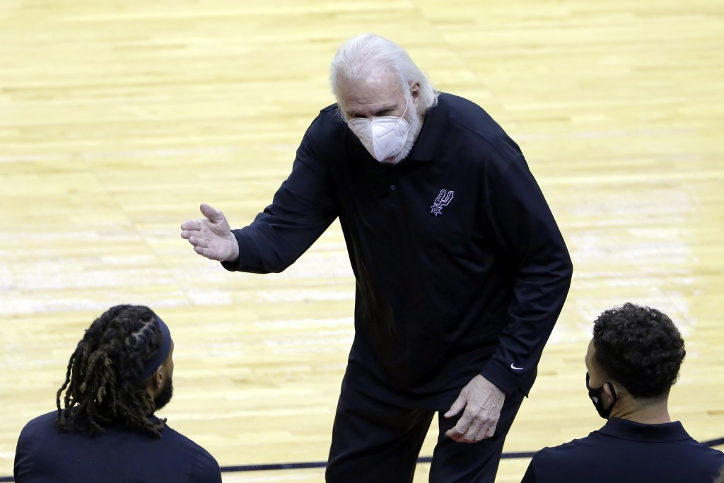 San Antonio Spurs head coach Gregg Popovich in a mask as he talks with players on the bench during the second half of an NBA basketball game against t...