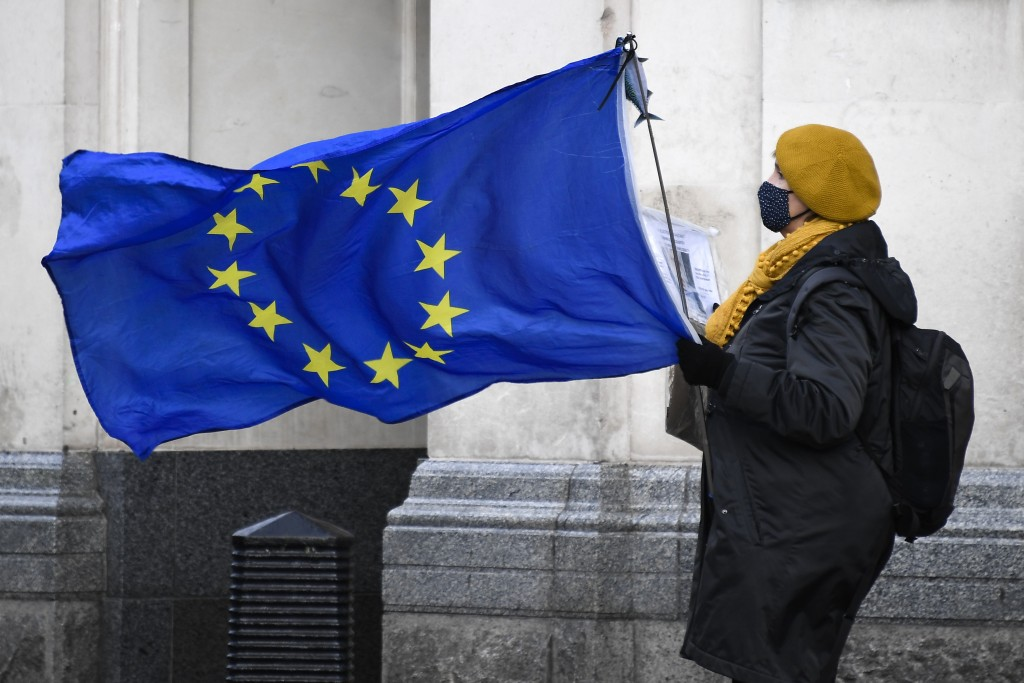 An anti-Brexit demonstrator holds an EU flag in Parliament Square, in London, Wednesday, Dec. 16, 2020. Ursula von der Leyen said Wednesday she saw cl...