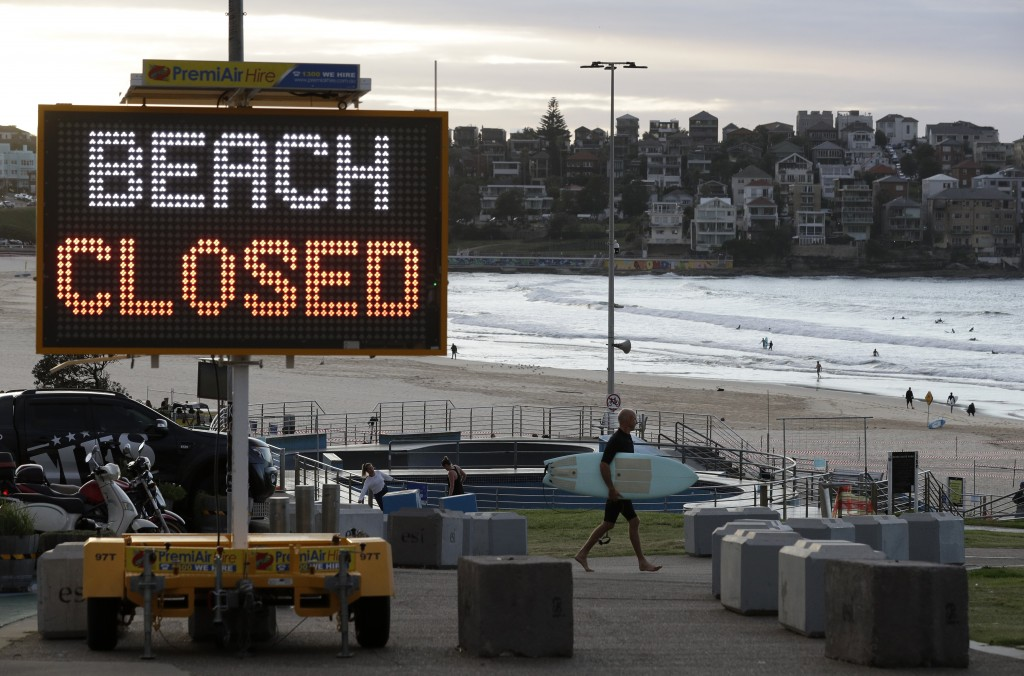 A sign indicates that Bondi Beach is closed as a surfer arrives for the 7 a.m. opening in Sydney, Tuesday, April 28, 2020, as coronavirus pandemic res...