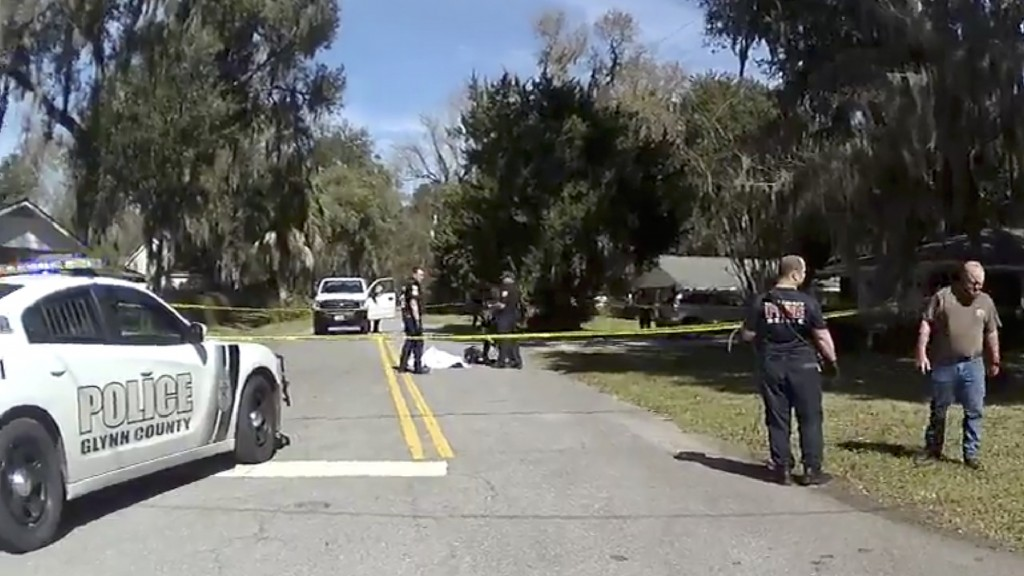 In this Feb. 23, 2020 image taken from Glynn, Ga., County Police body camera video, authorities, rear, stand over the covered body of Ahmaud Arbery, a...