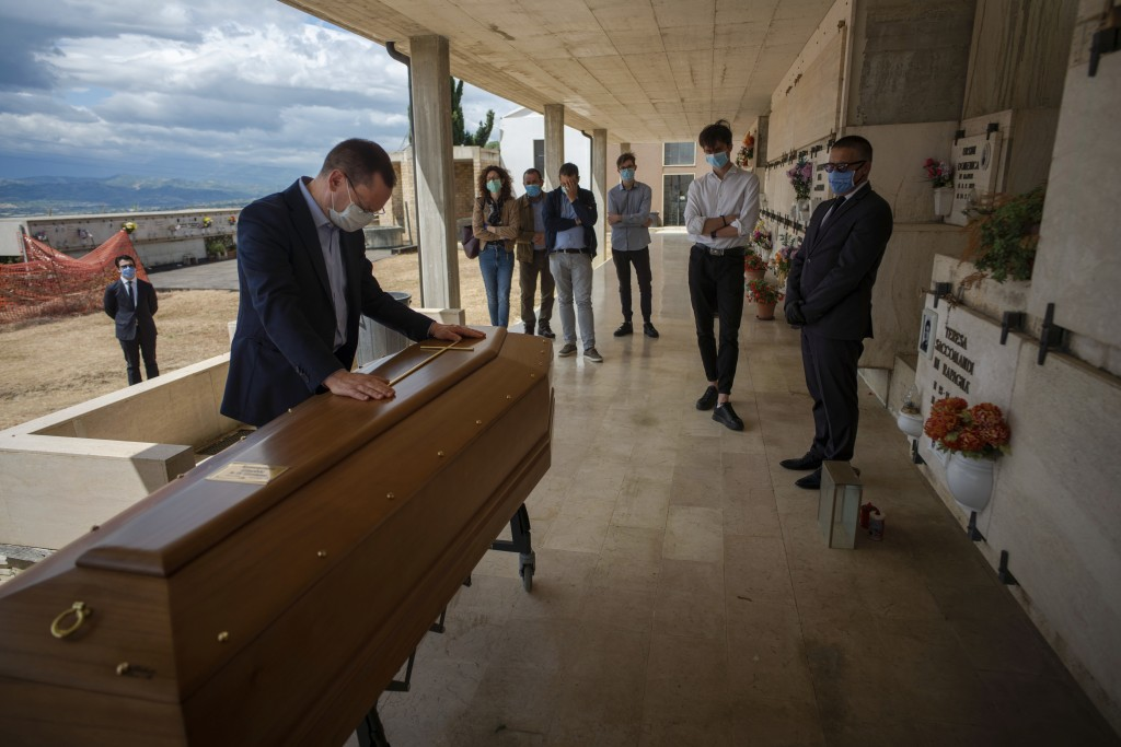 Sabatino Di Girolamo, mayor of Roseto degli Abruzzi, left, lays his hands on the the casket of his mother, Annunziata Ginoble, before her inhumation a...