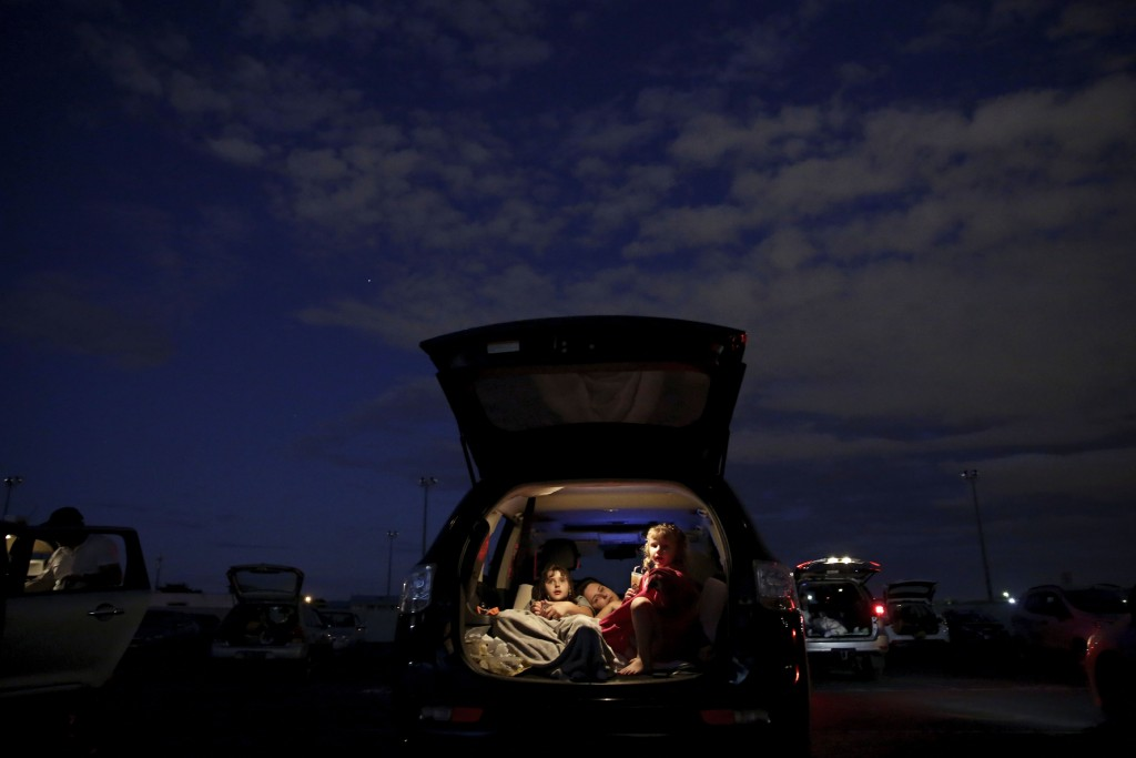 A family watches a movie from the back of their car at a drive-in movie theater where drivers must leave one space empty between them amid the new cor...