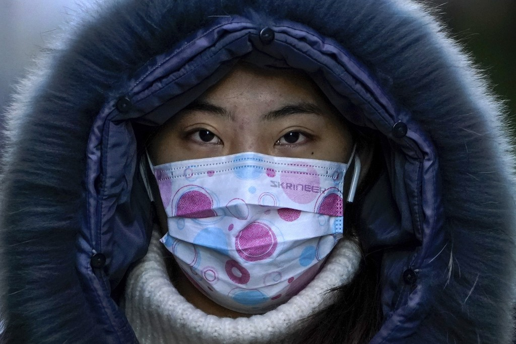 A woman wearing a face mask to help curb the spread of the coronavirus walks on a street during the morning rush hour in Beijing, Wednesday, Dec. 16, ...