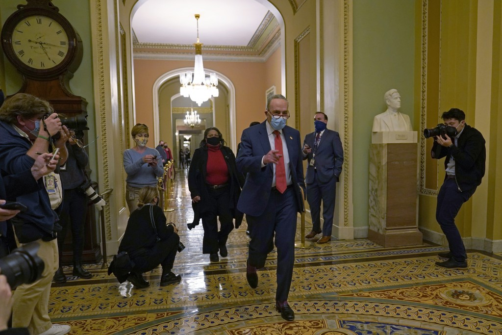 Senate Minority Leader Sen. Chuck Schumer of N.Y., walks past reporters on Capitol Hill in Washington, Tuesday, Dec. 15, 2020. (AP Photo/Susan Walsh)