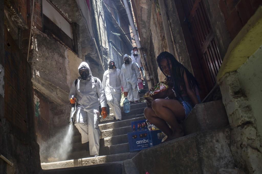 Volunteers spray disinfectant in an alley to help contain the spread of the new coronavirus, at the Santa Marta slum in Rio de Janeiro, Brazil, Saturd...