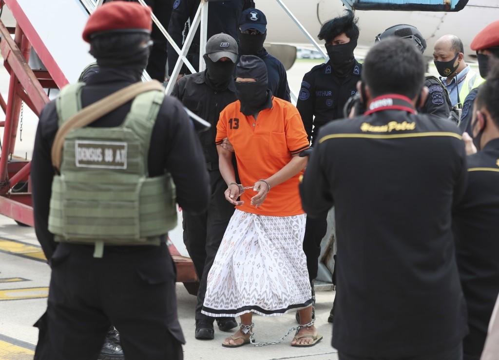 Police officers escort suspected militant Zulkarnaen,center, who is also known as Aris Sumarsono, upon arrival at Soekarno-Hatta International Airport...