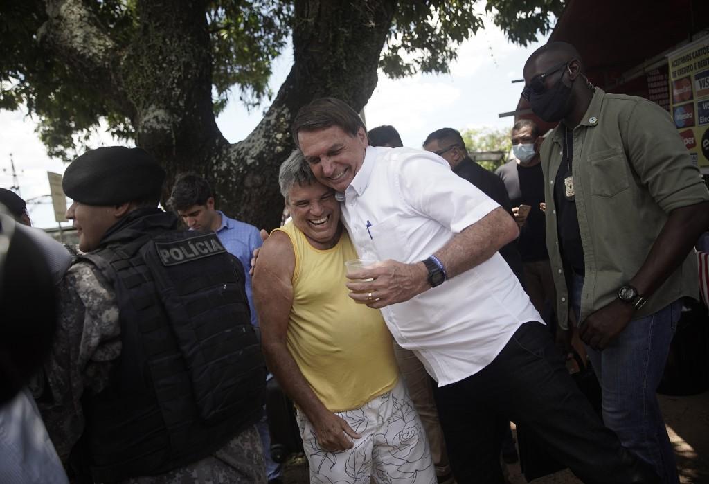 President Jair Bolsonaro embraces a supporter after voting during the run-off municipal elections in Rio de Janeiro, Brazil, Sunday, Nov. 29, 2020. Bo...