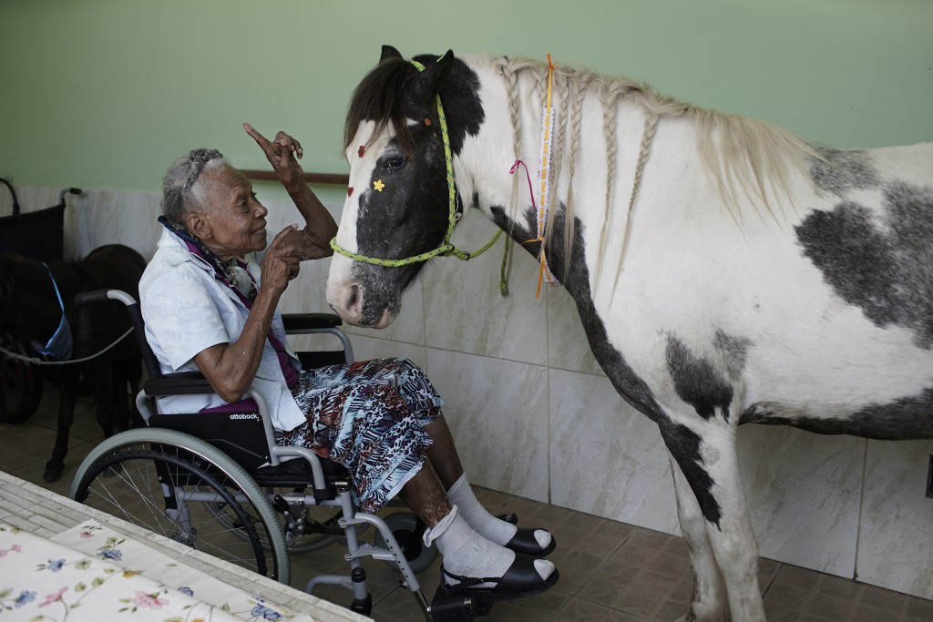 "A woman speaks affectionately to a horse named ""Tony"" at the Maria Vieira Bazani nursing home in Rio de Janeiro, Brazil, Thursday, Oct. 22, 2020. The ..."