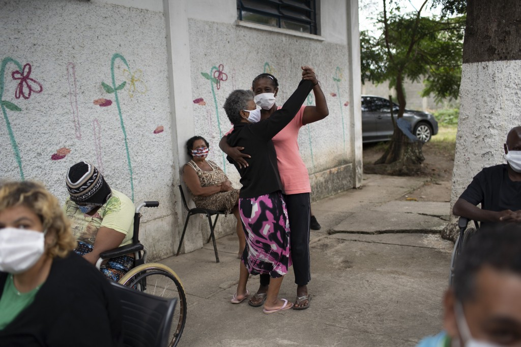 Elderly women dance as an armed forces band plays at the Complex Stella Maris shelter for the elderly in Rio de Janeiro, Brazil, Thursday, May 14, 202...