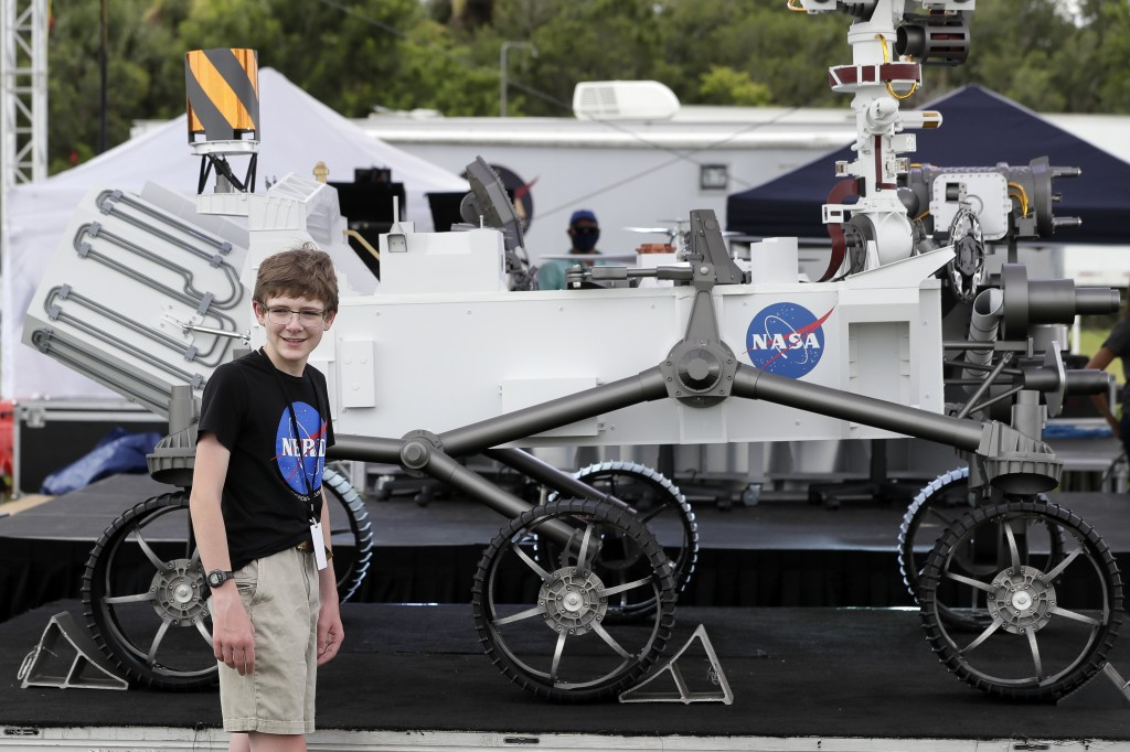 "FILE - In this July 28, 2020, file photo, Alexander Mather, of Burke, Va., stands next to a model of the Mars 2020 rover he named  ""Perseverance"" in a..."