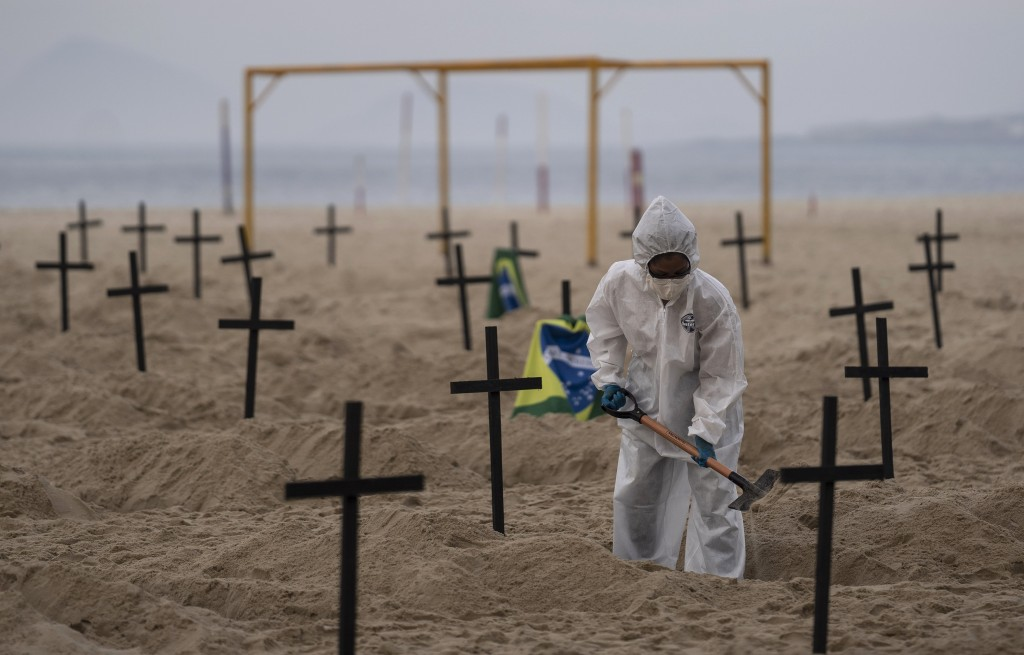 An activist digs symbolic graves on Copacabana beach, in front of a soccer goalpost, during a protest organized by the NGO Rio de Paz against the gove...