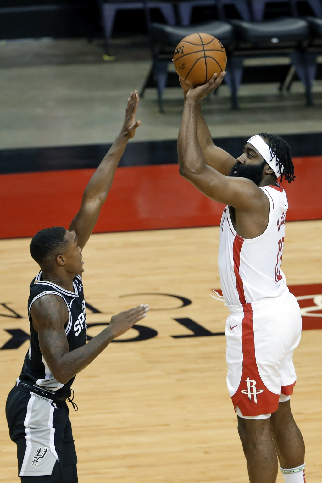 Houston Rockets guard James Harden, right, puts up a shot over San Antonio Spurs guard Lonnie Walker IV, left, during the first half of an NBA basketb...