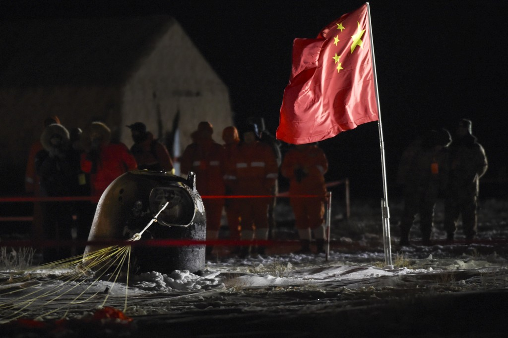 In this photo released by Xinhua News Agency, recovery crews look at the capsule of the Chang'e 5 probe after its successful landing at the main landi...