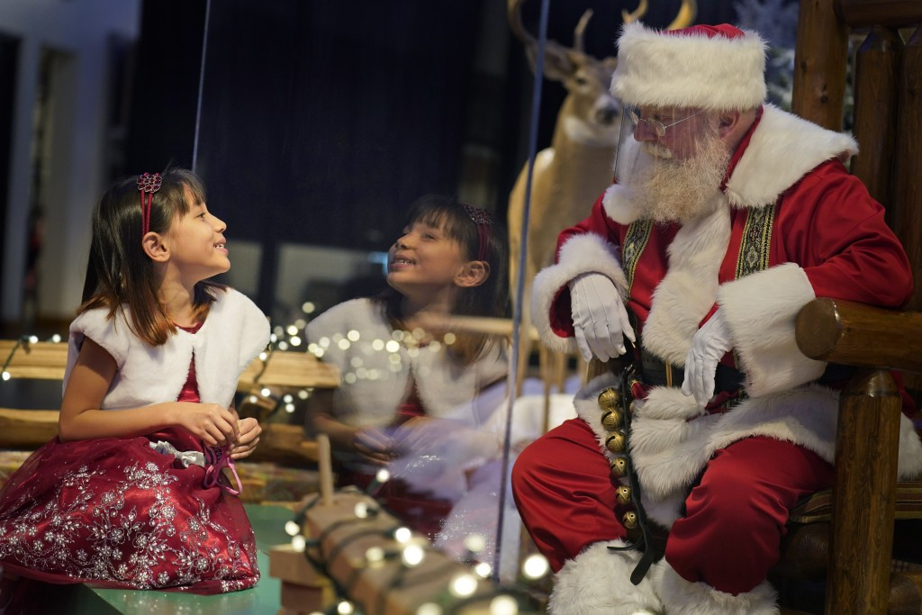 Gracelynn Blumenfeld, 8, visits with Santa through a transparent barrier at a Bass Pro Shop in Bridgeport, Conn., on Nov. 10, 2020. In this socially d...