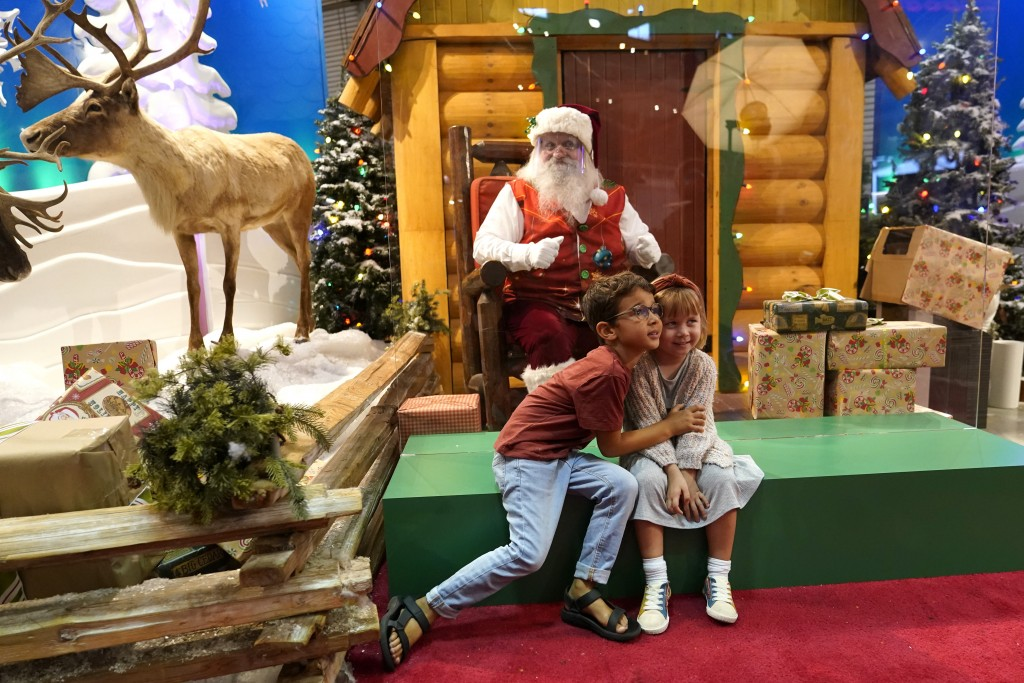 Theo and Sophy Morris, visiting from Hawaii with their family, pose for a photograph with Santa Claus, who is sitting behind a transparent barrier, at...