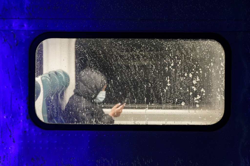 A passenger rides in a Long Island Rail Road train car as snow starts to fall Wednesday, Dec. 16, 2020, in the Queens borough of New York. (AP Photo/F...