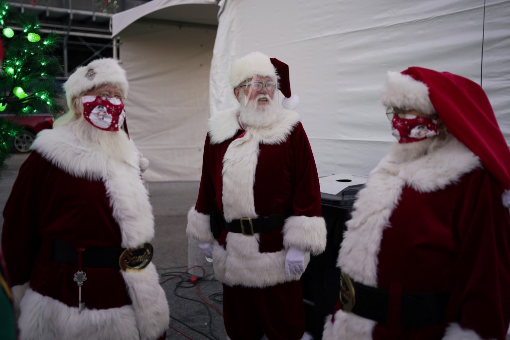 Santa Claus' from left, Larry Hansen, Charlie Bush and Bill Sandeen, wear masks as a precaution against coronavirus while waiting before the opening o...
