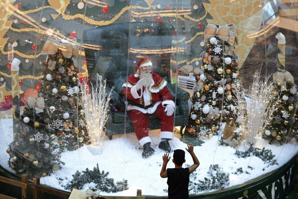 Abilio Nunes, a Santa Claus performer, waves to children from inside a bubble, a protective measure against the spread of COVID-19, at a shopping cent...