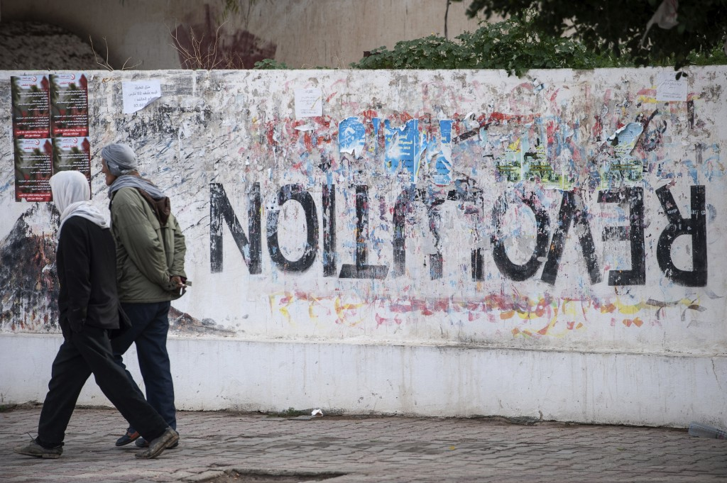 Residents walk past graffiti in Sidi Bouzid, Tunisia, Friday, Dec. 11, 2020. Hundreds of desperate Tunisians have set themselves on fire in the past 1...
