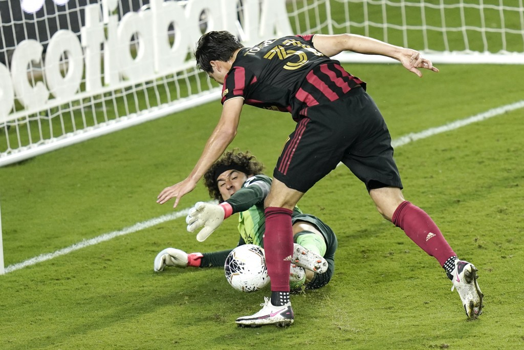 Club America goalkeeper Guillermo Ochoa, lower left, blocks a shot on goal by Atlanta United forward Erick Torres (31) during the second half of a CON...