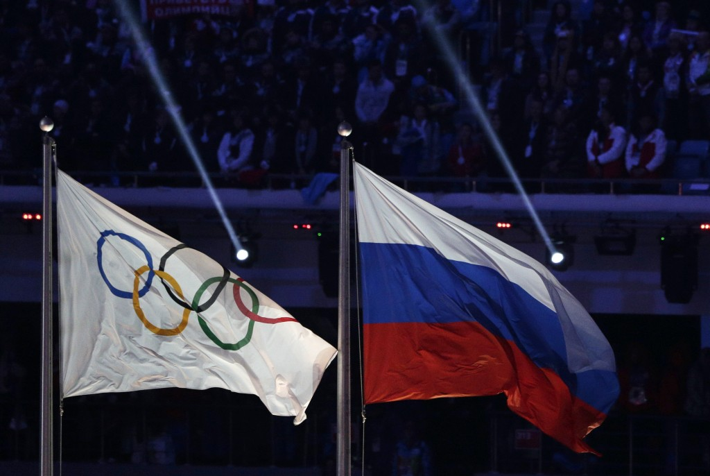 FILE - In this Feb. 23, 2014 file photo the Russian national flag, right, flies after it is hoisted next to the Olympic flag during the closing ceremo...