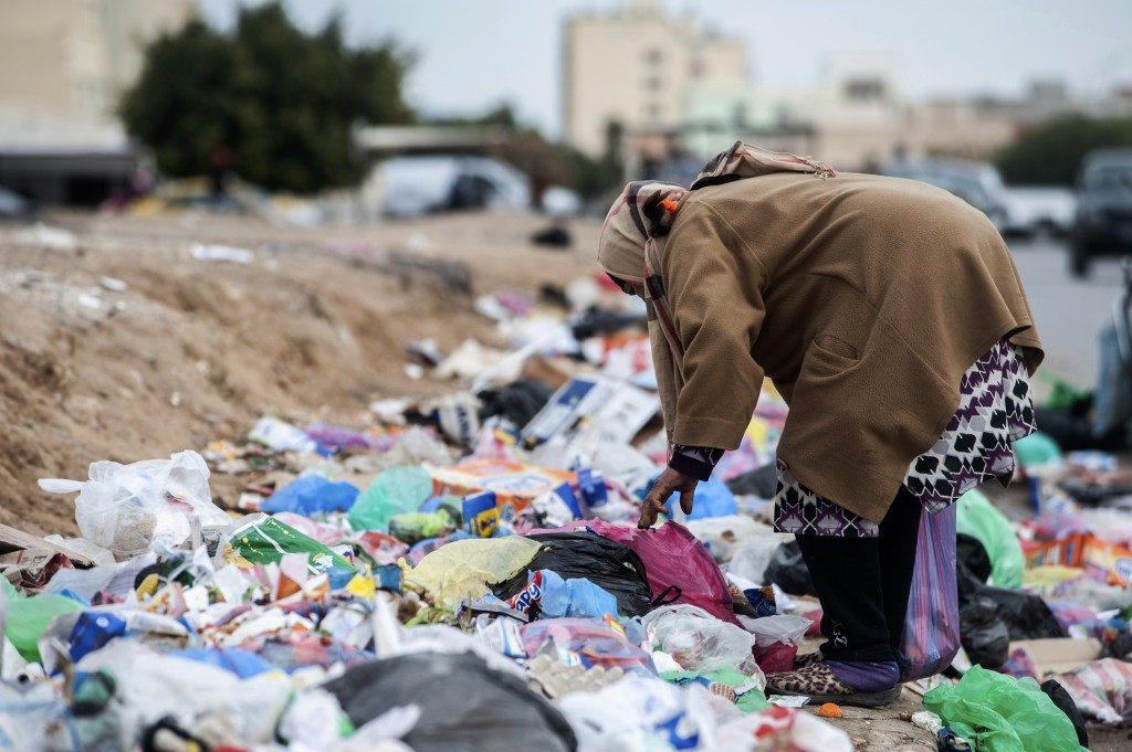 A woman picks through garbage in Kasserine, Tunisia, on Friday Dec. 11, 2020. Hundreds of desperate Tunisians have set themselves on fire over the pas...