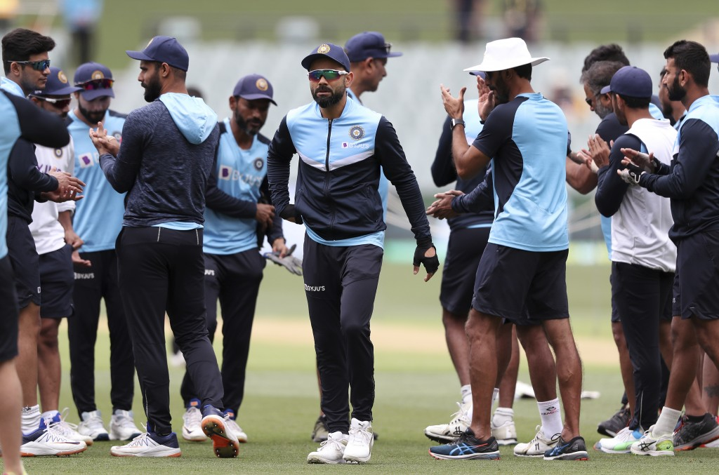 India's players, lead by captain Virat Kohli, center, warm up before their cricket test match against Australia at the Adelaide Oval in Adelaide, Aust...