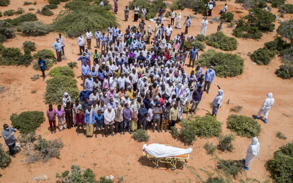 In this photo taken Thursday, April 30, 2020, mourners gather to bury an elderly man believed to have died of the coronavirus in Mogadishu, Somalia. Y...