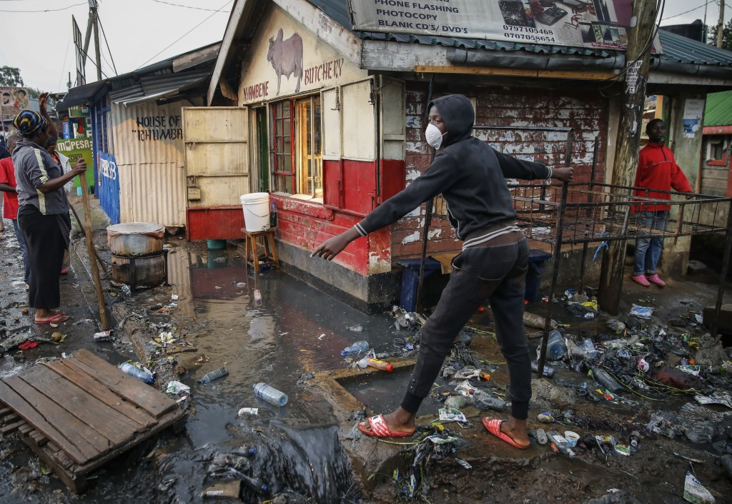 A boy wears a mask as a preventative measure against the spread of the new coronavirus, as he navigates a flood of water mixed with garbage following ...